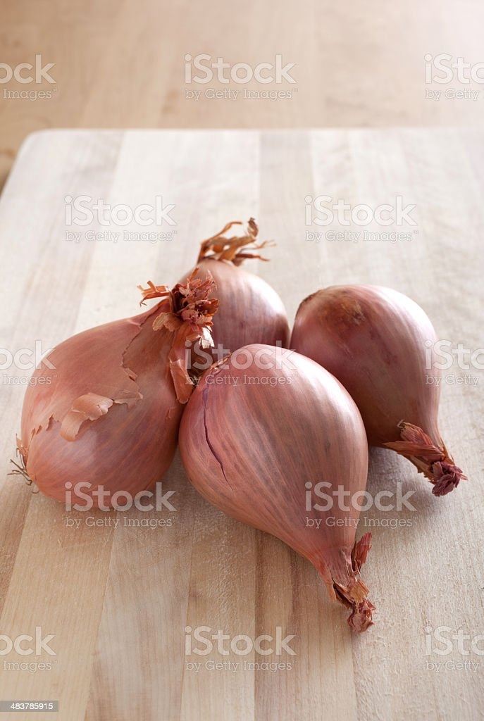 Four Shallots on a Cutting Board stock photo