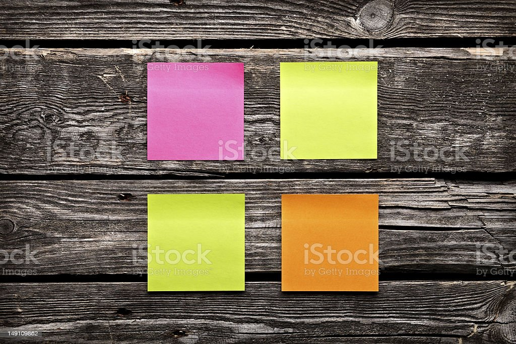 Four sheets of different colors sticky note paper. stock photo