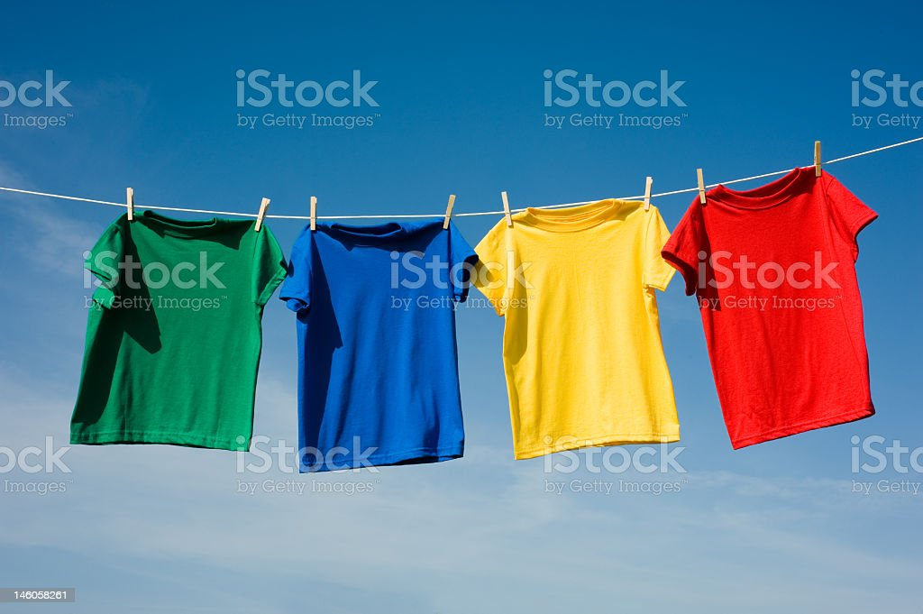 Four shirts in primary colors hanging from a clothesline stock photo