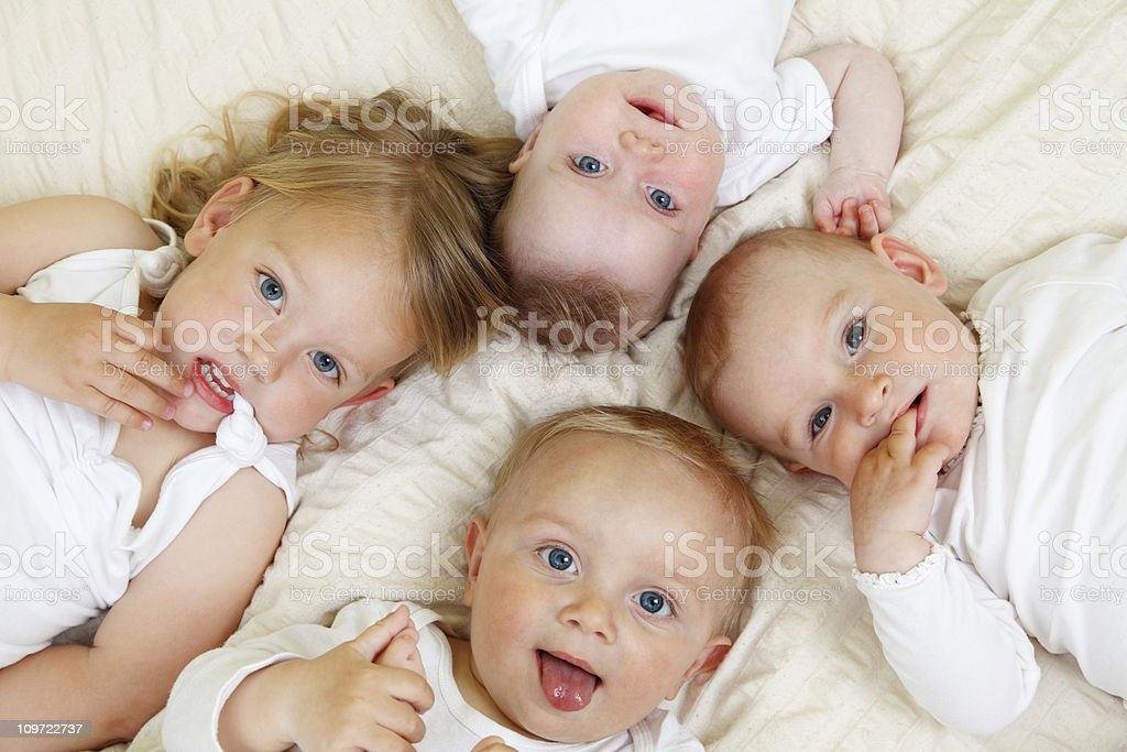 Four siblings laying together in white on a white bed stock photo
