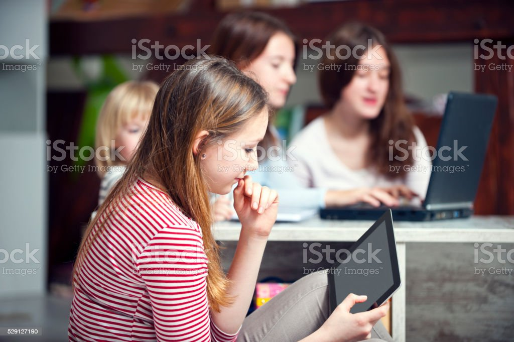 Four sisters using digital tablet and laptop stock photo