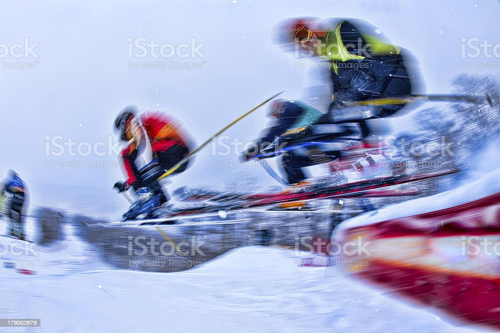 Four ski racers going over a jump. stock photo