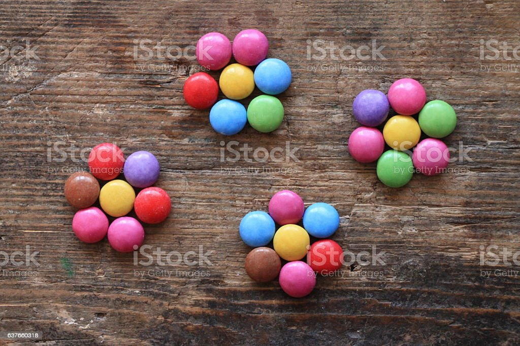 Four small flowers made with colorful candies on wooden table stock photo