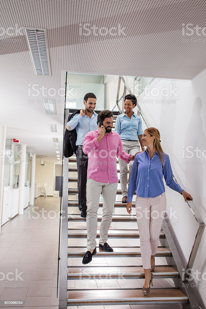 Four smiling business people walking down the stairs. stock photo