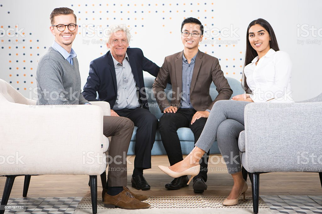 Four Smiling Diverse Business Partners in Lounge stock photo