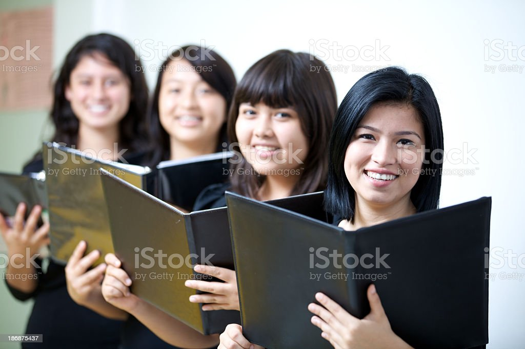 Four smiling female members of a choir, singing with books stock photo