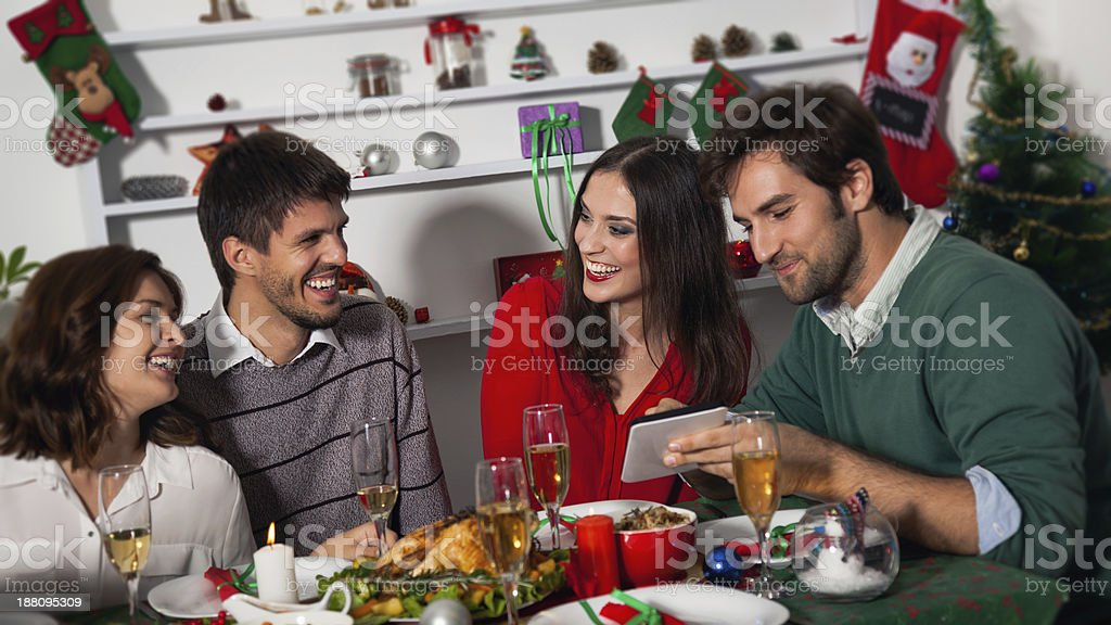 Four smiling friends having a Christmas dinner stock photo