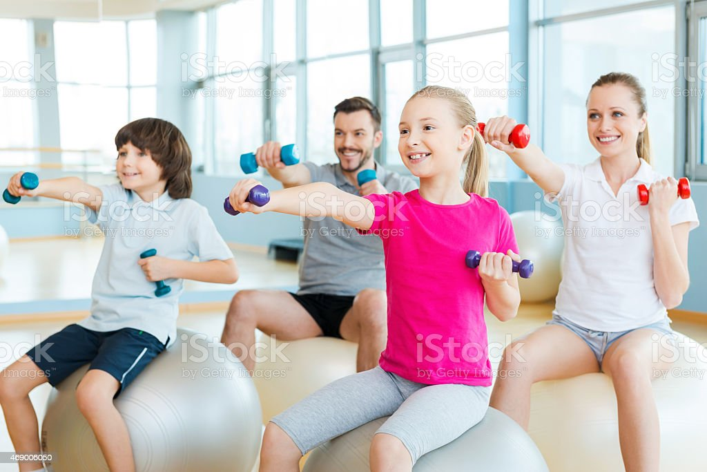 Four smiling gym goers with hand weights atop balance balls stock photo