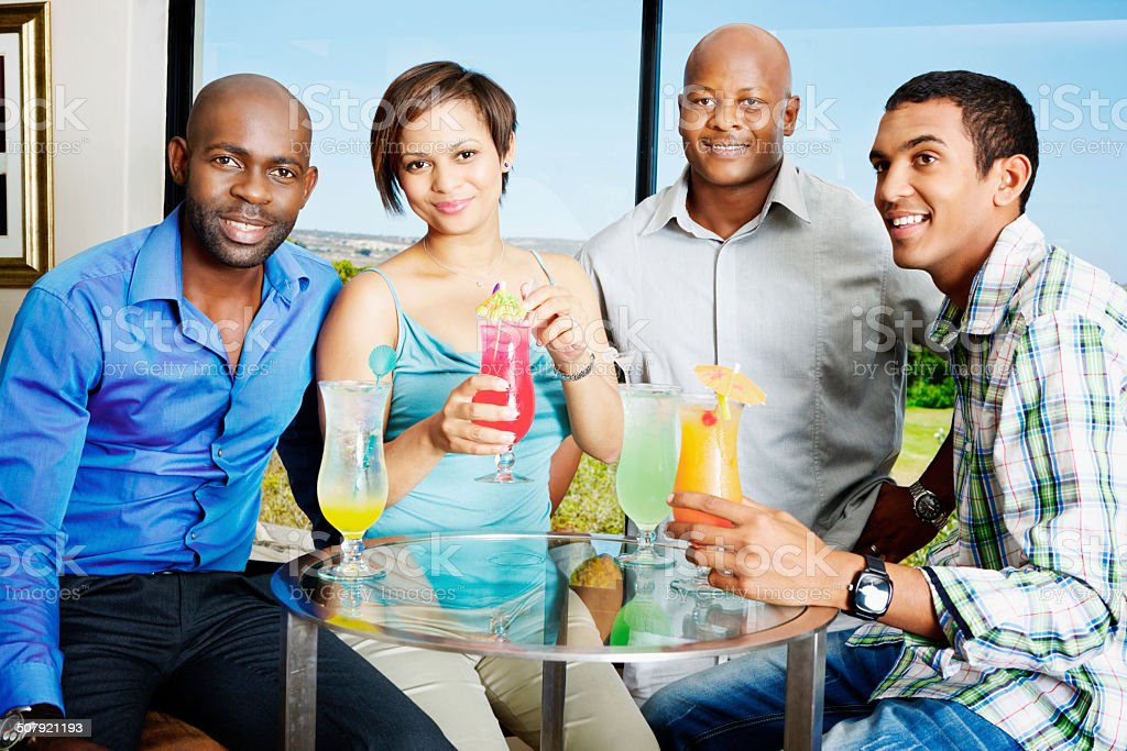 Four smiling yound adults drinking cocktails in bar lounge stock photo