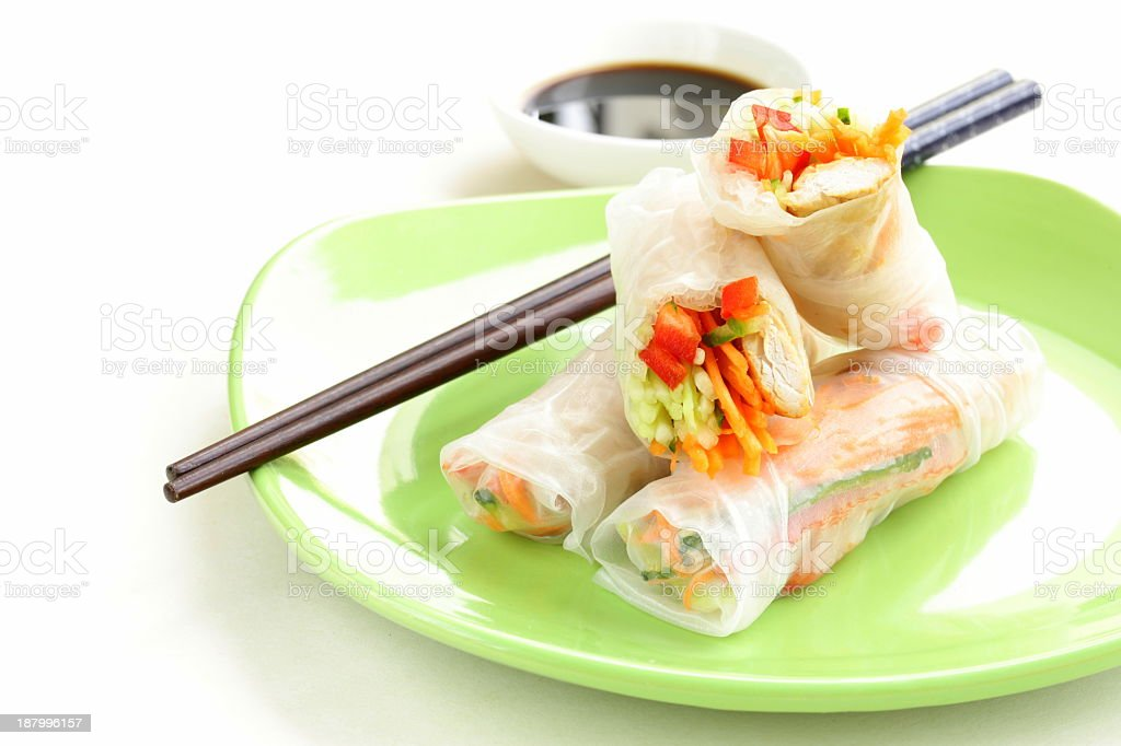 Four spring rolls on a green plate, with chopsticks stock photo