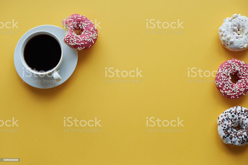 Four sprinkled dontus and cup of coffee stock photo