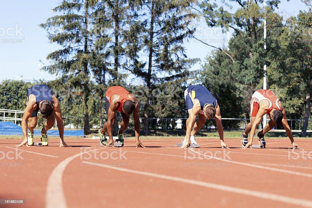four sprinters in starting blocks stock photo