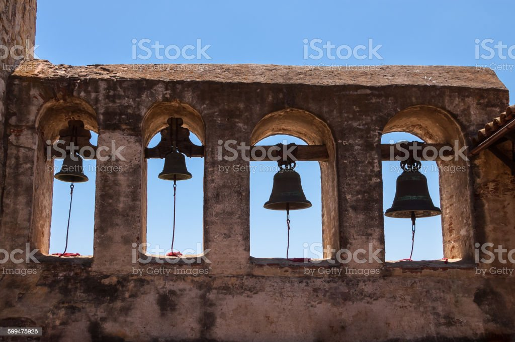 Four stationary bells hang from on an old Mission ruin stock photo