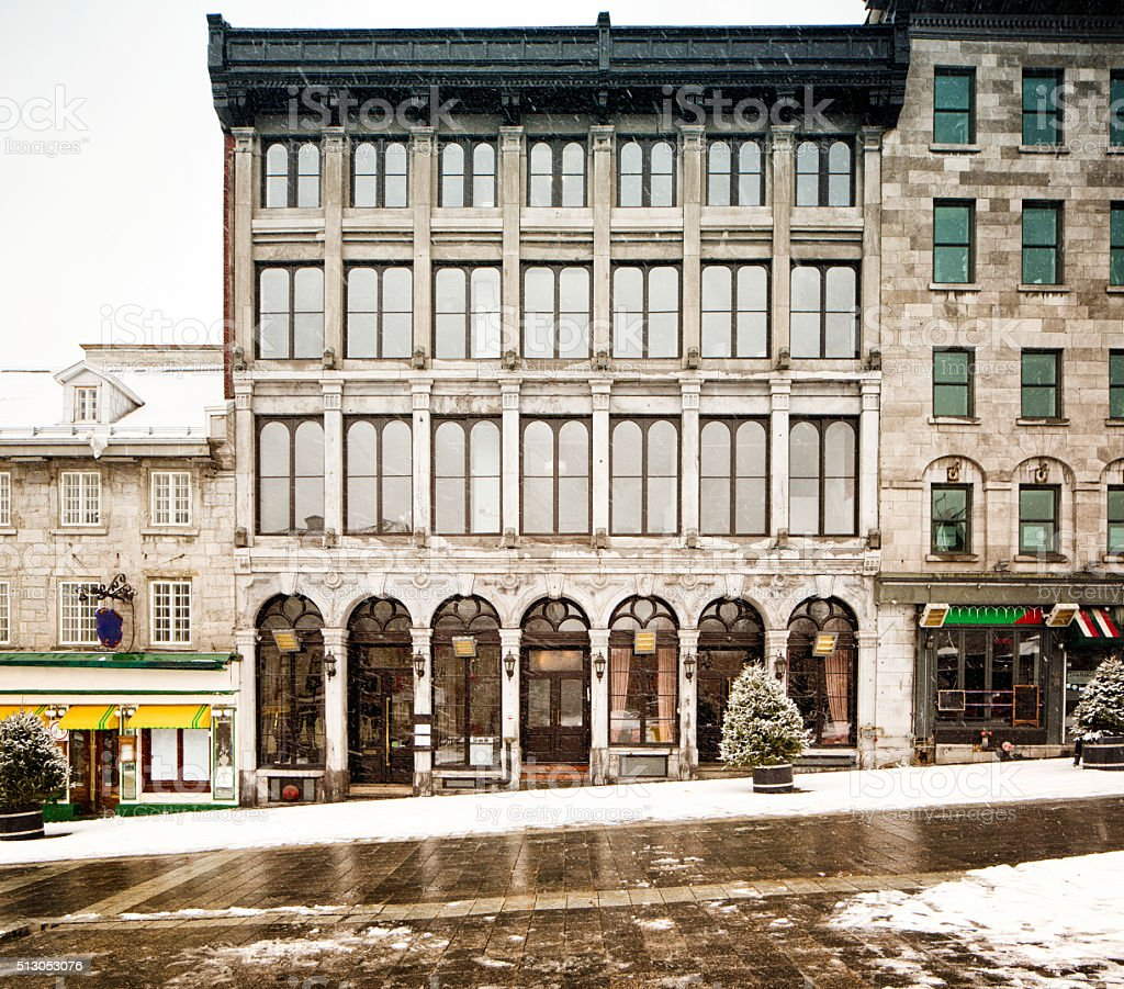 Four stories building in Old Montreal during snow storm stock photo