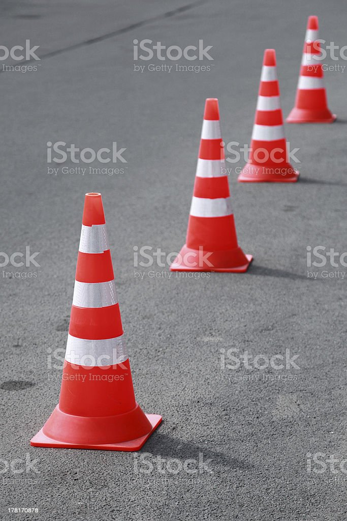 Four striped orange cones stand on gray asphalt road royalty-free stock photo