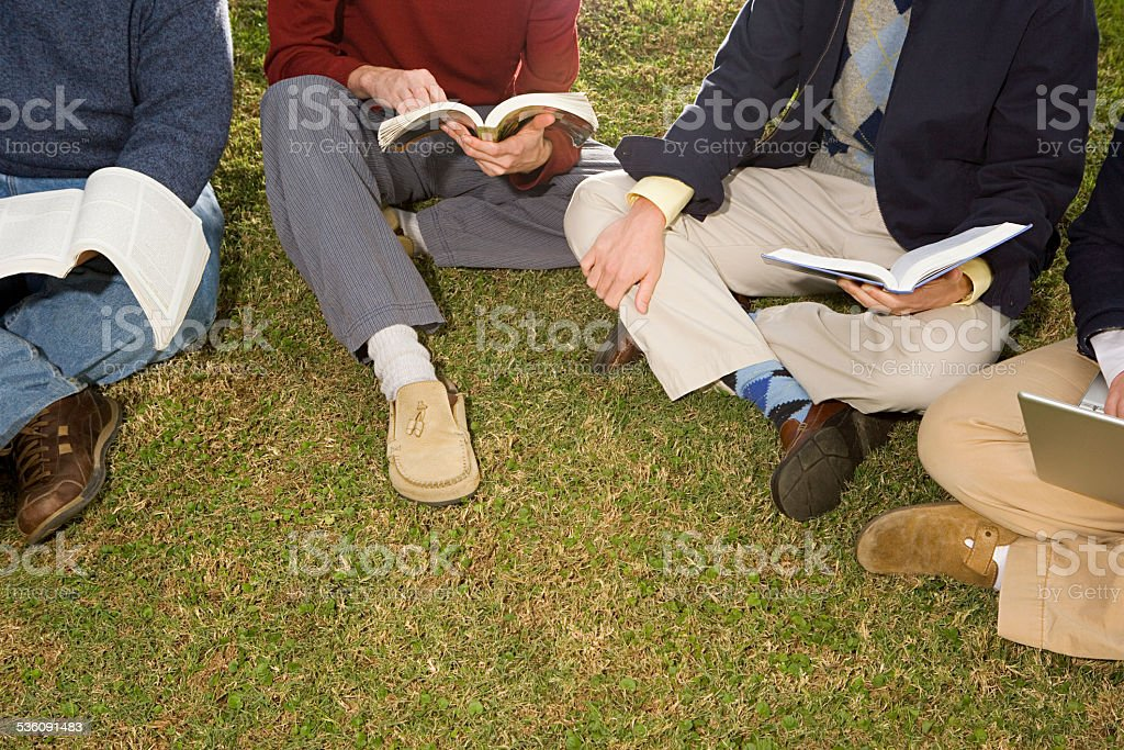 Four students sat outdoors stock photo