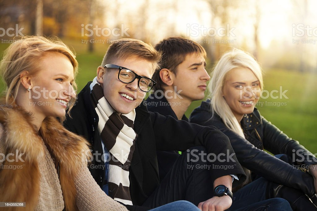 Four students sitting in the park royalty-free stock photo