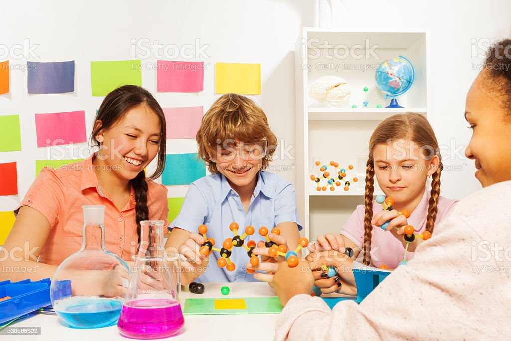 Four students studying chemistry at the classroom stock photo