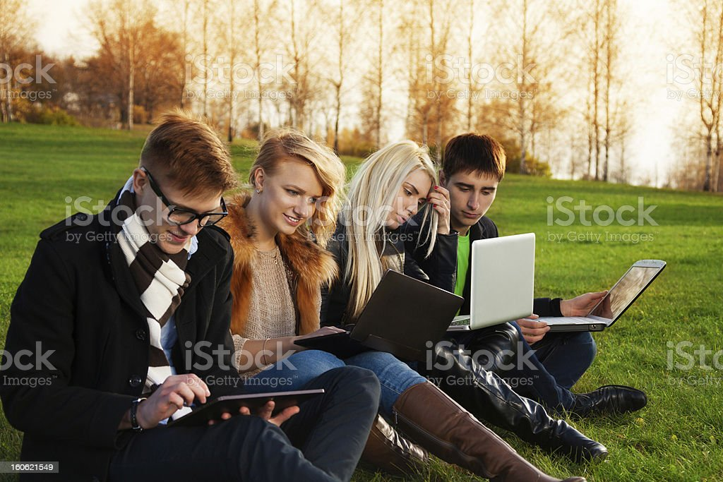 Four students working on laptops in the park royalty-free stock photo