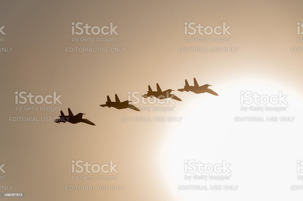 Four Su-27 aircrafts fly on bright Sun disk background royalty-free stock photo