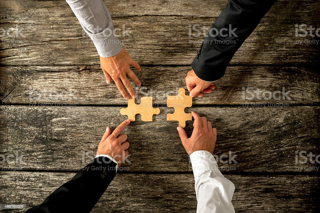 Four successful business men joining two puzzle pieces each being...