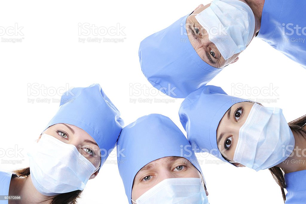 four surgeon's heads in masks together making circle royalty-free stock photo