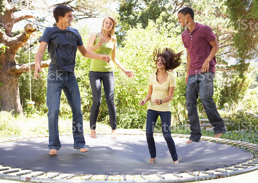 Four Teenage Friends Jumping On Trampoline In Garden stock photo