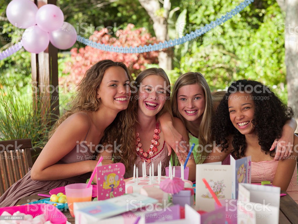 Four teenage girls at birthday party smiling outdoors stock photo