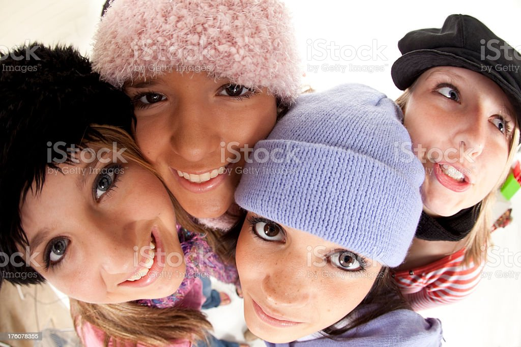 Four teenage girls in winter hats and scarfs. royalty-free stock photo
