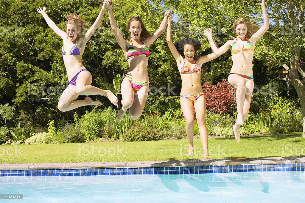 Four teenage girls jumping into pool royalty-free stock photo