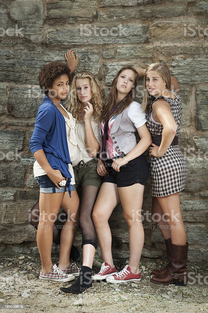 Four Teenage Young Women Friends in Shorts against Stone Wall royalty-free stock photo
