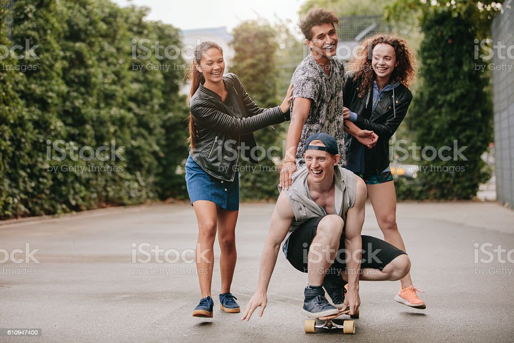 Four teenagers enjoying outdoors with skateboard stock photo