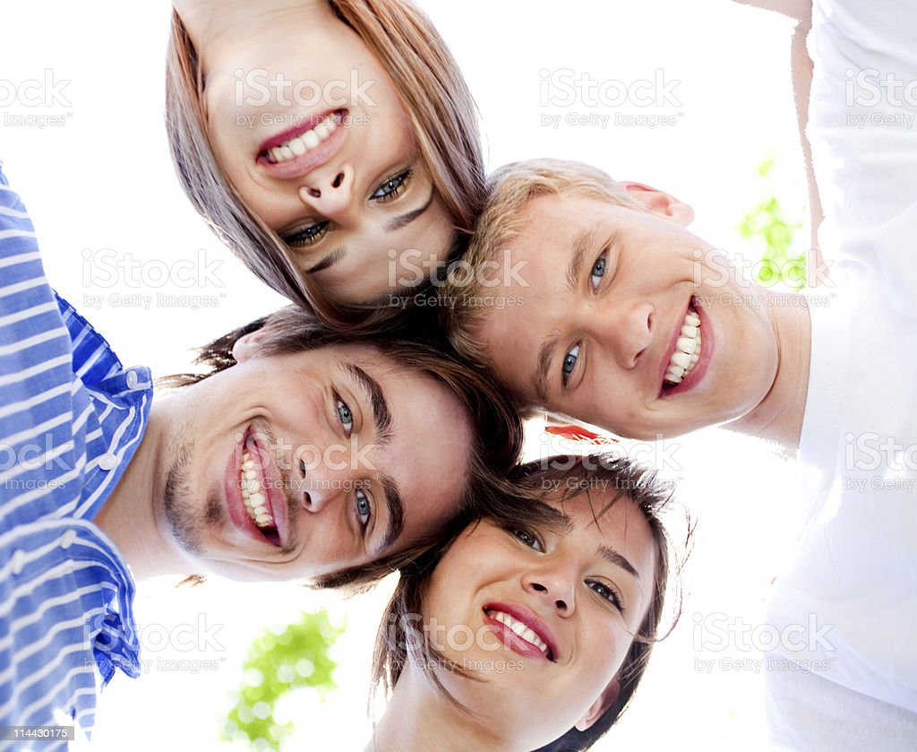Four teenagers standing in huddle royalty-free stock photo