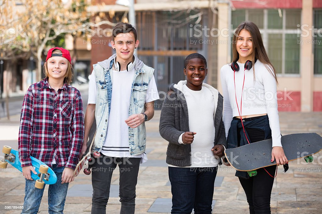 Four teens with skateboards outdoors stock photo