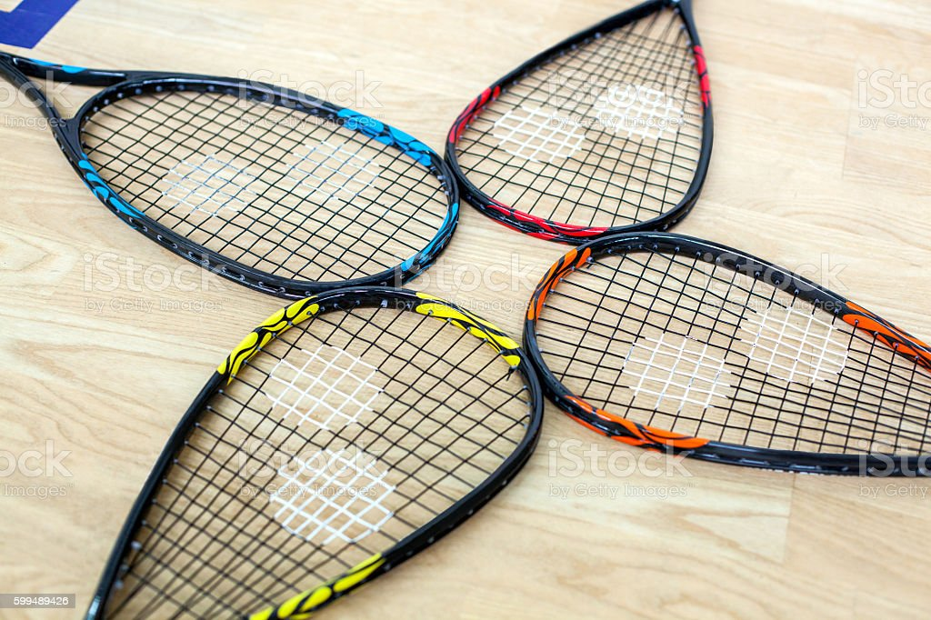 Four tennis rackets are lying on wooden court stock photo