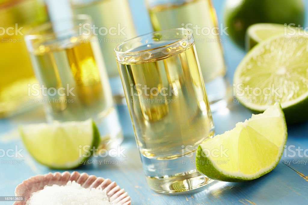Four tequila shots with lime and salt on a blue table stock photo