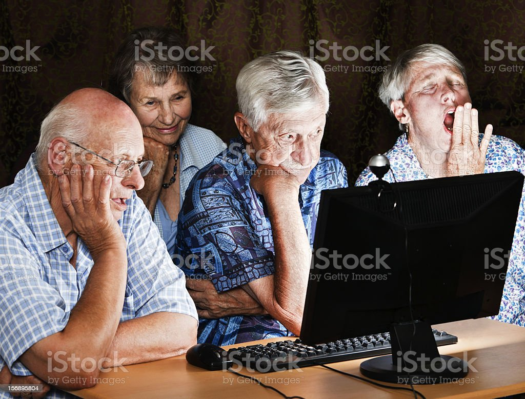 Four tired, bored seniors sit round a computer at night stock photo