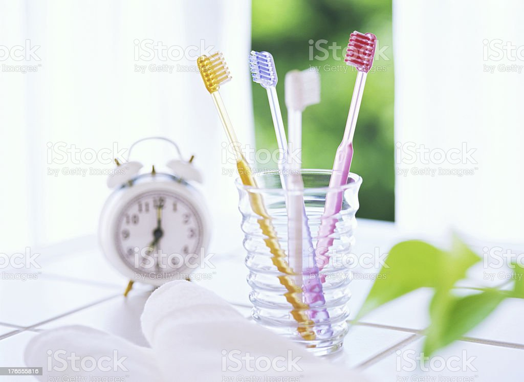 Four toothbrushes and alarm clocks royalty-free stock photo