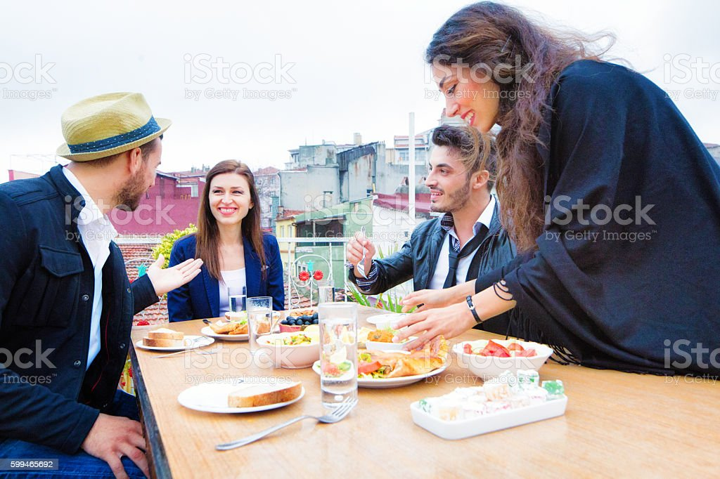 Four Turkish friends meeting for lunch on Istanbul rooftop stock photo