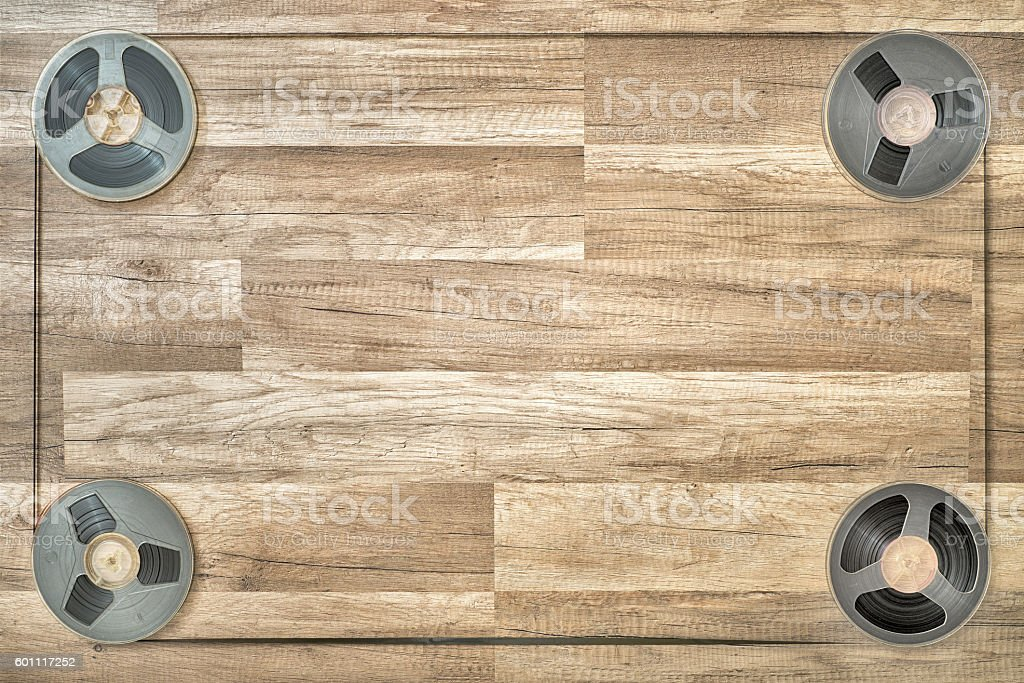 Four vintage magnetic audio reels in the corners on the grunge wooden...