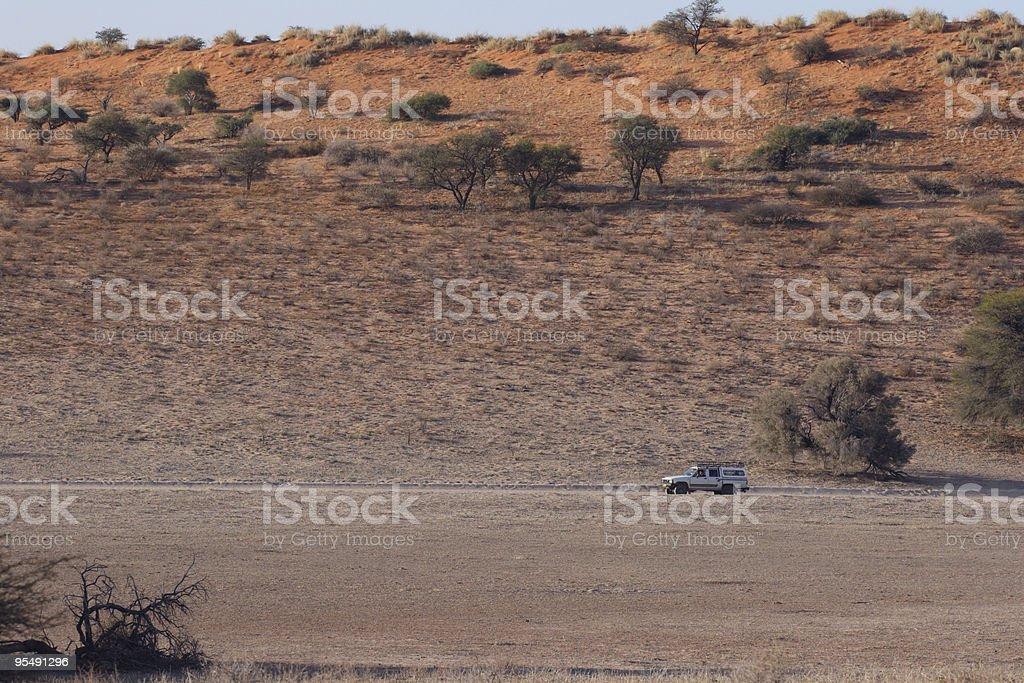 Four wheel pick up driving near a large sand dune stock photo