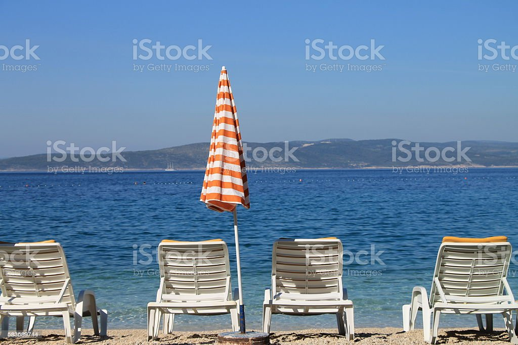 Four white beach chairs and sun umbrella in Brela, Croatia stock photo