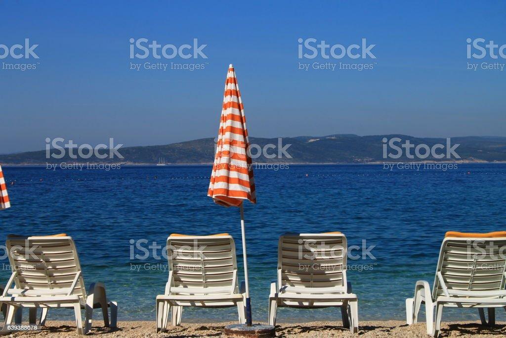 Four white beach chairs and sun umbrella near Adriatic sea stock photo