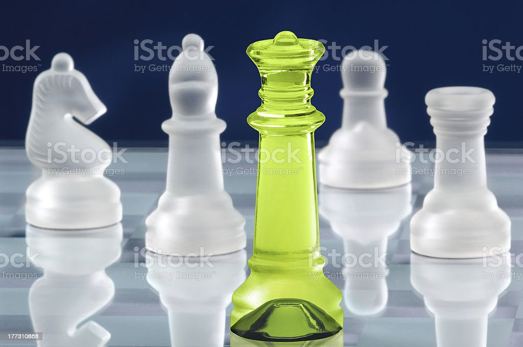 Four white chess pieces and one lime green in the middle royalty-free stock photo