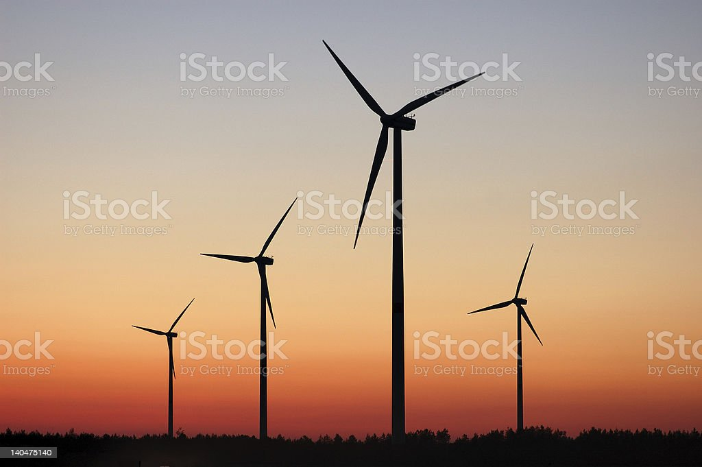 Four wind turbines silhouetted at sunset stock photo