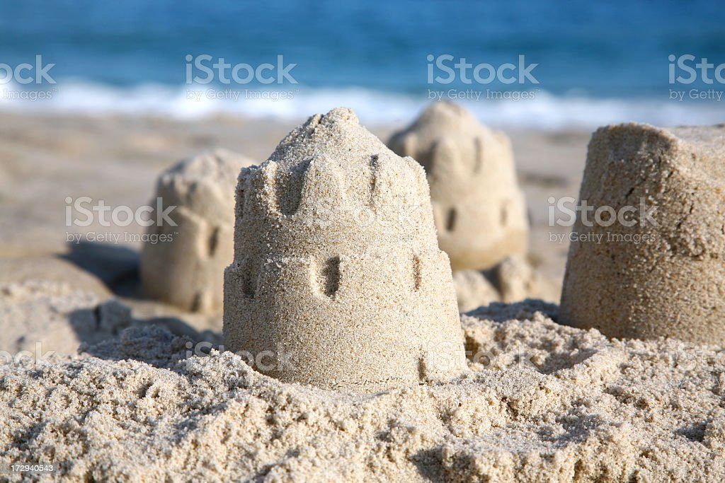 Four windswept sand castles standing on the beach royalty-free stock photo