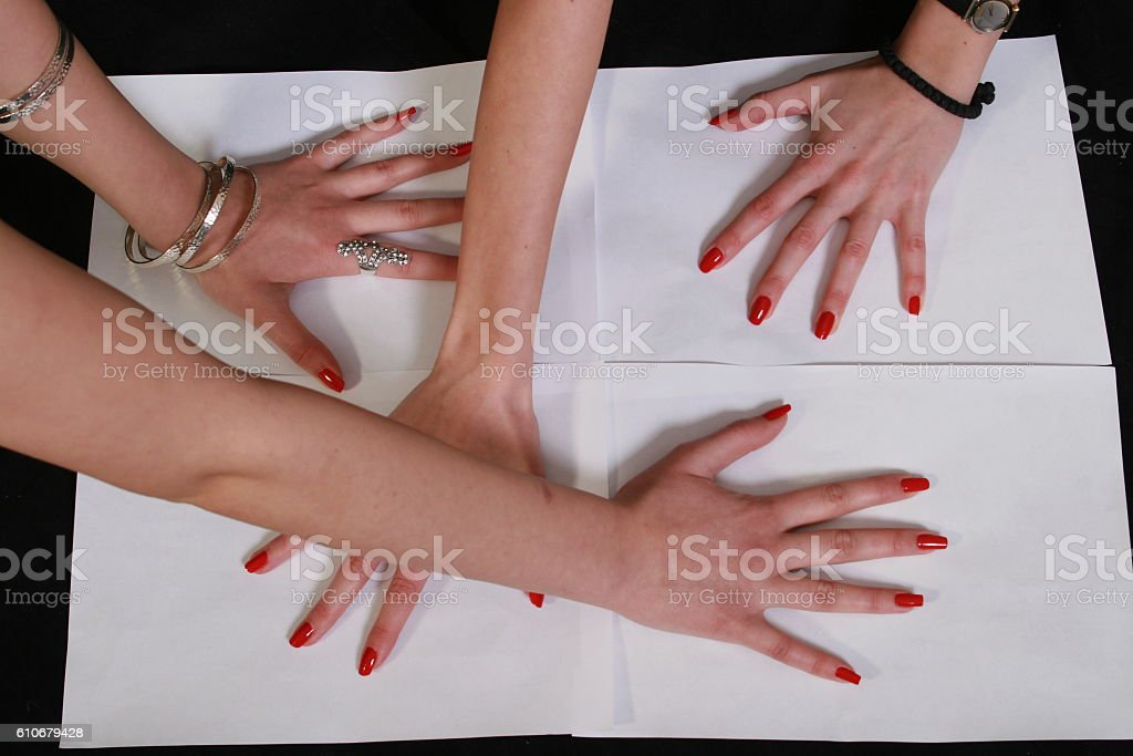 Four woman hands on white paper stock photo