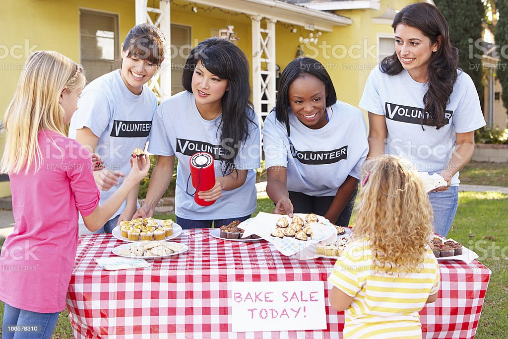 Four women and two young girls running a bake sale stock photo