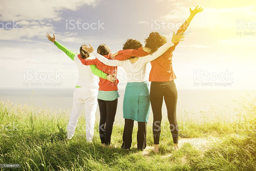 Four women embrace on sunny day stock photo