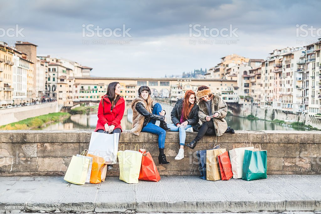 Four women friends take a break on bridge in Florence stock photo